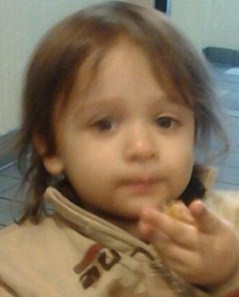 Slightly blurred photo of Michael Guzman, a Caucasian toddler with wispy brown hair, wearing a brown sweater and holding his hand out to the camera.