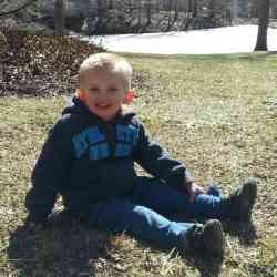 Photo of Brayson Price, a young boy with short-cropped blond hair and fair skin, wearing jeans and a blue jacket. He is sitting outside on a grassy lawn.