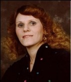 Portrait photo of Shirley Williamson, a middle-aged woman with pale skin and curly, shoulder-length auburn hair.