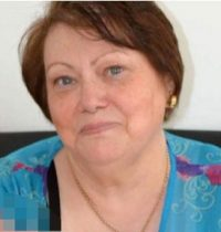 Photo of Leah Cohen, a middle-aged woman with fair skin and short, straight brown hair. She is wearing a turquoise blouse and small gold hoop earrings.