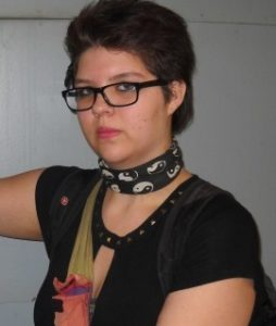 Photo of Ryanna Grywacheski, a young woman wearing dark-rimmed glasses, a choker, and a dark blouse. Her hair is dark brown and cut short; her skin is fair. She is wearing light makeup.