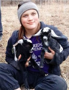 Photo of Savannah Leckie, a teenage girl with fair skin and light-brown hair, wearing a knit cap and sweatshirt. She is holding two black-and-white goat kids.