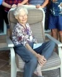 Photo of Vivian Nelson, an elderly woman with pale skin and short curly white hair. She is thin, wearing a floral blouse and blue slacks, and sitting in a big beige chair with one leg propped up on the chair.