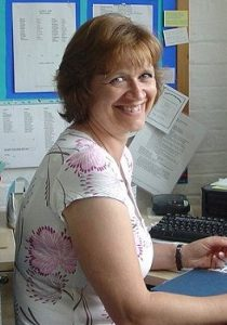Photo of Diane Stewart. She is a middle-aged woman with fair skin and auburn hair, wearing a flowered blouse and sitting at a computer. She is smiling at the camera.