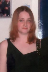 Photo of Sonya Todd, a young woman with shoulder length light-brown hair, wearing a black sleeveless dress. She has pale skin and blue eyes.