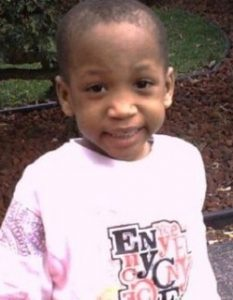 Photo of Davarion Davis, a boy with brown skin and black hair in a buzz cut, photographed outdoors, smiling at the camera. He is wearing a pink sweatshirt with a logo printed on the front.