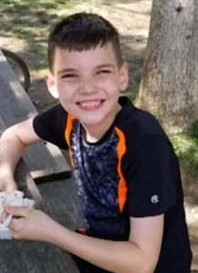 Photo of Dylan Davis, a boy with short brown hair and fair skin, photographed outdoors. He is grinning at the camera.
