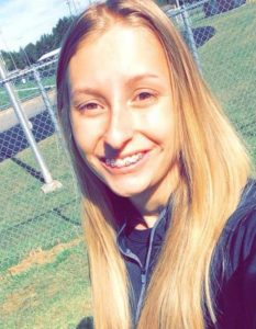 Photo of Kayla Hensley, a teen girl with long, straight blond hair, fair skin, and braces on her teeth. Behind her is a green lawn and a fence. She is wearing a dark blue top and smiling.