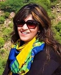 Photo of Sana Iqbal, a young woman with light skin and wavy dark-brown hair. She is wearing a big pair of sunglasses, a colorful blue and yellow scarf, and a jacket. The photo is taken outdoors.