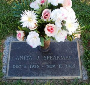 "Photo of Anita Spearman's gravestone, which reads, ""Anita J. Spearman, December 8, 1936 to November 15, 1985."" There are flowers in an attached vase."