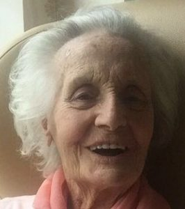 Photo of Ruby Williams, a very elderly woman with pale skin and wispy, curly white hair. She is wearing a peach sweater, and has been photographed in the middle of laughing at something off-camera.