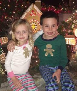 Photo of Luke and Bree Dawson, two small children. Bree is a girl with blond hair and fair skin; Luke has dark hair and fair skin. They are wearing Christmas-themed gingerbread cookie sweaters and have their arms around each other.