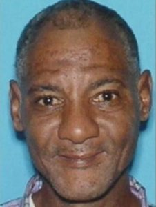 Photo of Pernell Robinson, a man with medium-brown skin and dark brown eyes. His graying dark hair is cut very short. He has a stubbly mustache and is smiling slightly.