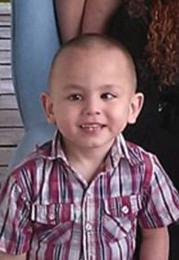 Photo of Jordan Rodriguez, a small boy with light skin and brown eyes. He is smiling. He has a lazy eye. His brown hair is cut very short, and he is wearing a red and white checked shirt.