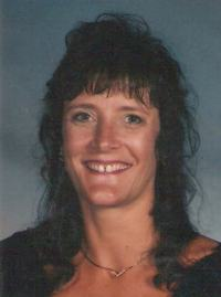 Photo of Deborah Crouch, a middle-aged woman with light skin and curly dark-brown hair. She is wearing a gold pendant necklace and smiling, showing a gap between her front teeth.