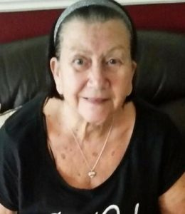 Photo of Margaret Sims, an elderly woman with pale skin and dark-gray hair pulled back in a hair band. She is wearing a black shirt and a gold pendant necklace.