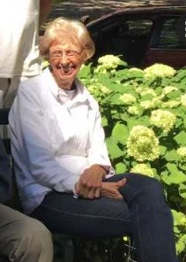 Photo of Barbara Wilmes, a light-skinned, white-haired elderly woman wearing a white shirt and dark pants, smiling as she sits on a bench in front of a flower bush.