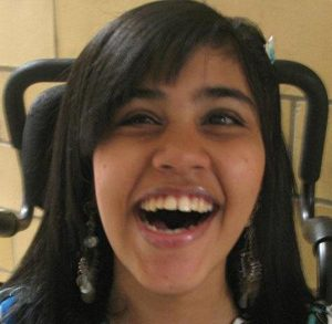 Photo of Qyzra Walji, a young woman with straight brown hair and tan skin, smiling broadly. A wheelchair head rest is visible behind her head.