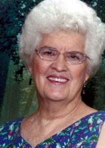 Photo of Jeanette Brown, an elderly woman with permed white hair and fair skin, wearing glasses and a blue patterned dress.