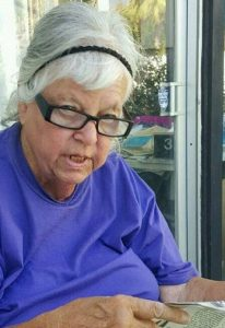 Photo of Lerae Bush, an elderly woman with fair skin and white hair held back in a headband. She is wearing reading glasses and holding a newspaper.