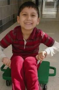 Photo of Abraham Cardenas, a little boy with olive skin and dark hair, smiling for the camera. He is wearing a red striped shirt and red pants, and is sitting on a scooter board.