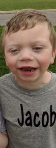 "Photo of Jacob Edwards, a small boy with fair skin and blond hair, smiling for the camera. He is wearing a gray T-shirt that says ""Jacob""."