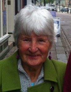 Photo of Betty Lyons, an elderly woman with short white hair and freckled skin, wearing a green coat and purple drop earrings.