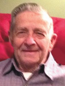 Photo of Leo McWilliams, an older man with gray hair and fair skin, wearing a plum-colored shirt and smiling for the camera.