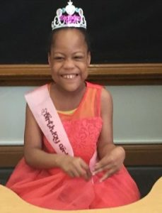 "Photo of Heaven Watkins, a small girl with brown skin and black hair pulled back under a silver crown. She is wearing a coral-colored dress and a sash that says ""Birthday Girl"". Her face is scrunched up in a wide smile."