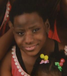 Photo of Jada Wright, a girl with short black hair and brown skin. She is wearing a coral-colored dress.