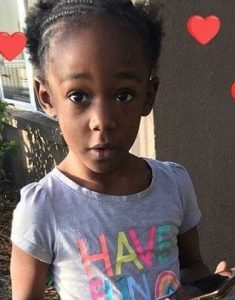 "Photo of Je'Hyrah Daniels, an African-American toddler with tightly braided hair, wearing a T-shirt printed with ""Have Fun"". She is looking at the camera with her mouth pursed in fascination, and holding a cell phone."