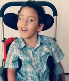 Photo of a young boy with light-brown skin and curly black hair sitting in a wheelchair with a headrest. He is smiling for the camera.