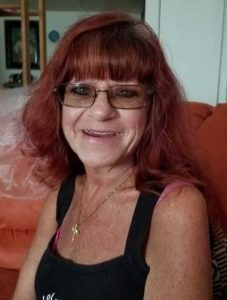 Photo of a middle-aged woman with dyed red hair, wearing a black tank top and a gold cross necklace. Her skin is freckled, and she wears sunglasses.