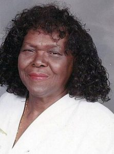 Photo of Mary Smith, a heavyset woman with dark-brown skin and shoulder-length hair in ringlets. She is wearing lipstick and a white blouse, and squinting at the camera.