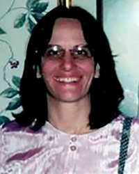 Photo of Vickie Balogh, a middle-aged woman wearing a pink silk blouse. Her skin is fair, but her face is flushed; she wears glasses and her straight brown hair is cut to shoulder length.