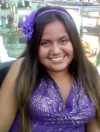 Photo of Bridget Charlebois, a young woman with tan skin and long, straight medium-brown hair. She is wearing a purple sequined tank top and a purple flower in her hair.