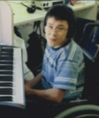 Photo of Nicholas Dean, a boy with dark hair and light-brown skin, sitting in a wheelchair in front of an electric keyboard. He is wearing glasses and a striped shirt.