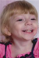 Photo of Kylee Forrest. She is a toddler with blonde hair and fair skin. She is smiling broadly. Her shirt is pink and ruffled.