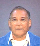 Photo of Manuel Reyes. He has tan skin and gray hair, and is wearing a blue sweater and white shirt.