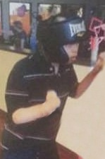 Photo of Brandon Strauss. He is a teenage boy with fair skin. He is wearing a striped polo shirt and his hair is hidden under his bulky helmet. He is leaning on something off to the right of the picture.
