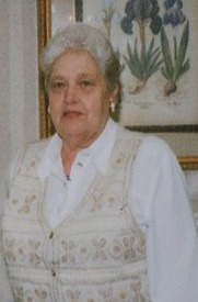 Photo of Luzie Wilson, an elderly heavyset woman. She has pale skin and short gray hair, and is wearing a white shirt and vest and gold earrings.