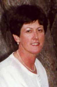 Photo of Jillian Thomas. She is a woman with pale skin and brown hair, wearing a white blouse and earrings.