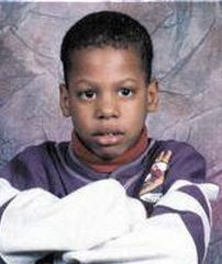 School photo of a boy with short, very curly black hair and brown skin and eyes. He is wearing a loose sweater, and has his arms folded in front of him. His expression is neutral.