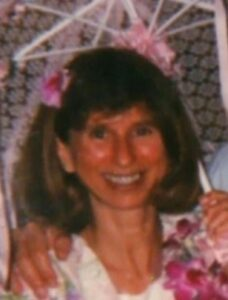 Photo of Cynthia Hrisco, a middle-aged woman with shoulder-length brown hair and bangs, holding a flowered parasol and wearing a flowered dress.