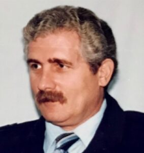 Photo of a middle-aged man with salt-and-pepper hair and mustache, wearing a suit.