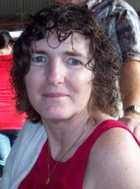 Photo of Elizabeth Knowles. She has pale skin, chin-length curly brown hair, and blue eyes. She is smiling slightly. She is wearing a pink sleeveless shirt and a silver necklace.