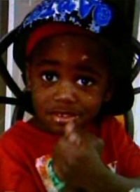 Photo of Teyshawn Young. He is a toddler with dark skin, wearing a red shirt and a blue hat.
