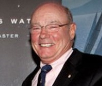 Photo of Richard Oland. He is a middle-aged white man wearing a suit and glasses.