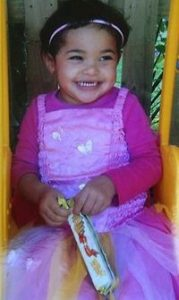 Photo of Tanilla Warrick-Deaves. She is a toddler with tan skin and curly black hair. She is wearing a pink dress, and holding a ribbon in her hands.