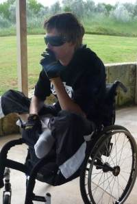 Photo of Tyron Honeywood, a young man sitting cross-legged in a wheelchair and smoking a cigarette. He is wearing sunglasses.